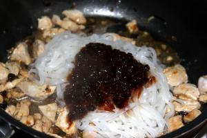 К куриному филе на сковородк добавляем отваренную лапшу и половину оставшегося соуса